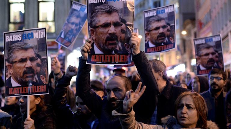 Protesterande människor som håller skyltar. Foto: AP
