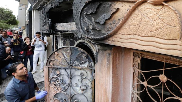 Man tittar på dörr som skadats efter bomben. Foto: AP.