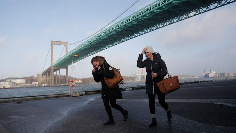 Två personer kämpar i blåsten nedanför Älvsborgsbron i Göteborg.