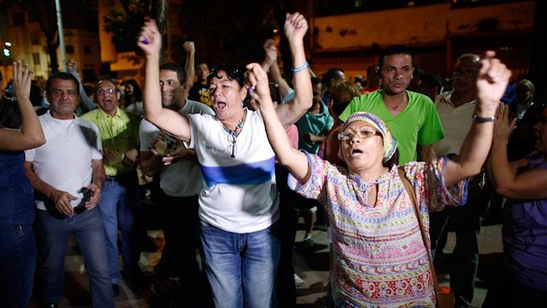 Kvinnor som jublar och sträcker upp sina händer. Foto: Ariana Cubillos.