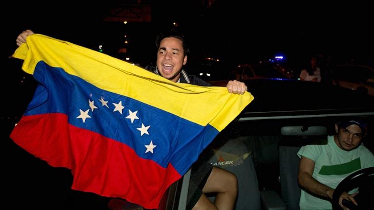 Man håller upp Venezuelas flagga efter oppositionens seger i parlamentsvalet. Foto: Fernando Llano/TT.