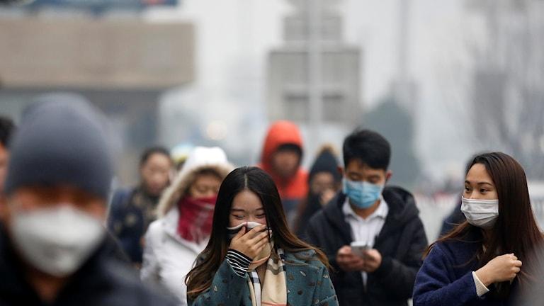 människor i andningsmask i Peking på gata i smog