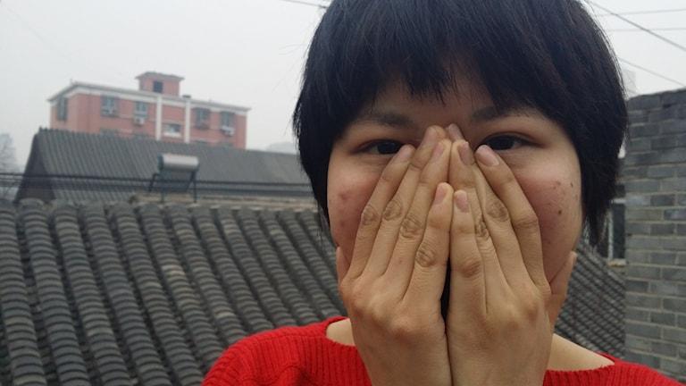 Wan Huanghua är 21 år står med händerna för munnen och smoggen ligger tjock över hustaken. Foto: Hanna Sahlberg/Sveriges Radio