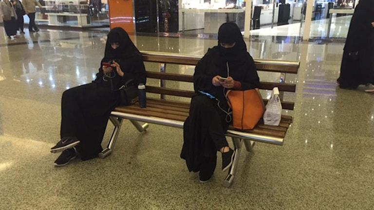 Två saudiska kvinnor sitter på en bänk med sina mobiltelefoner. Foto: Cecilia Uddén/Sveriges Radio.