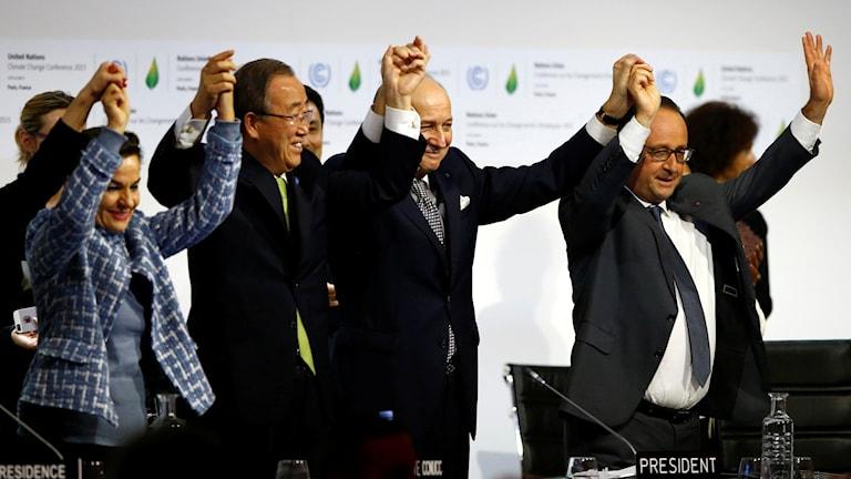 fyra människor firar det nya avtalet. Foto: Francois Mori/AP