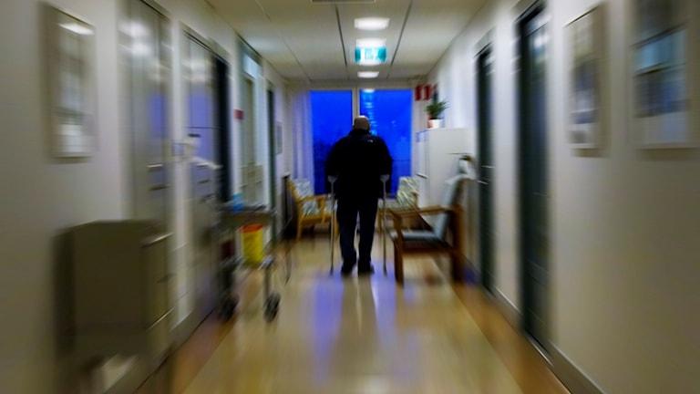 Äldre man går med käppar i korridoren på ett äldreboende