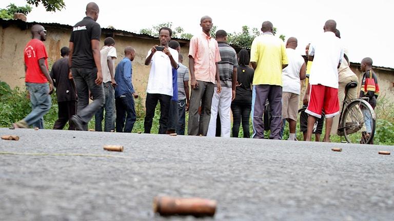 En grupp män står på gatan, där det ligger ammunition på marken.  Foto: TT.