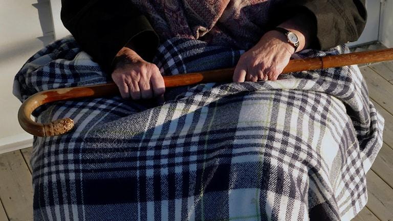Äldre kvinna i rullstol med en rutig filt över sina ben. Hon håller i en träkäpp. Foto: Hasse Holmberg/TT.