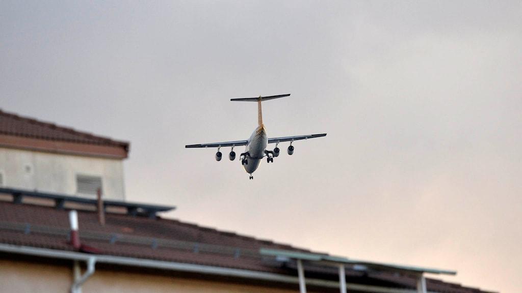 Ett flygplan syns över husen vid Zinkensdamm på Södermalm i Stockholm, på väg att landa på Bromma flygplats. Foto: Henrik Montgomery / TT