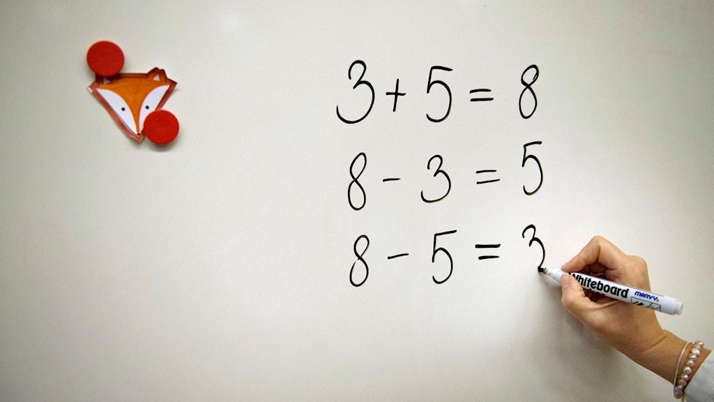 Lärare skriver på vita-tavlan.