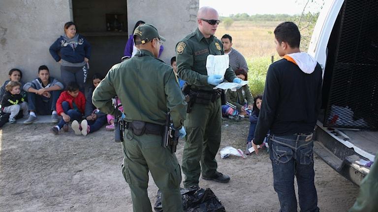 Amerikansk gränspolis kontrollerar en grupp personer som illegalt tagit sig över gränsen från Mexiko. Foto: John Moore/TT.