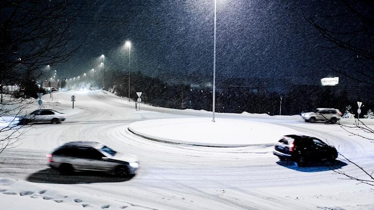 En rondel med fyra bilar som kör runt i snöoväder. Foto: TT.