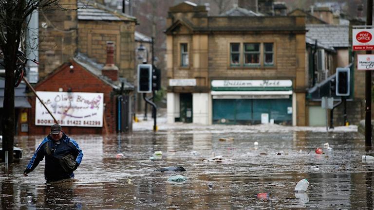 En man går vadandes på översvämmad gata i West Yorkshire.