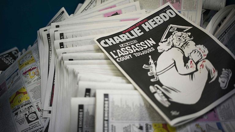 """På framsidan av Charlie Hebdos nya nummer kan man läsa: Ett år senare, mördaren är fortfarande på fri fot"""". Foto: AFP / MARTIN BUREAU/ TT."""
