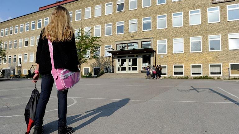 En ensam flicka på väg till skolan över en tom skolgård.