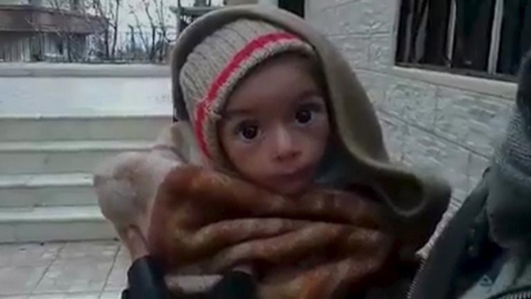 Ett litet barn inlindat i filtar. Foto: TT.
