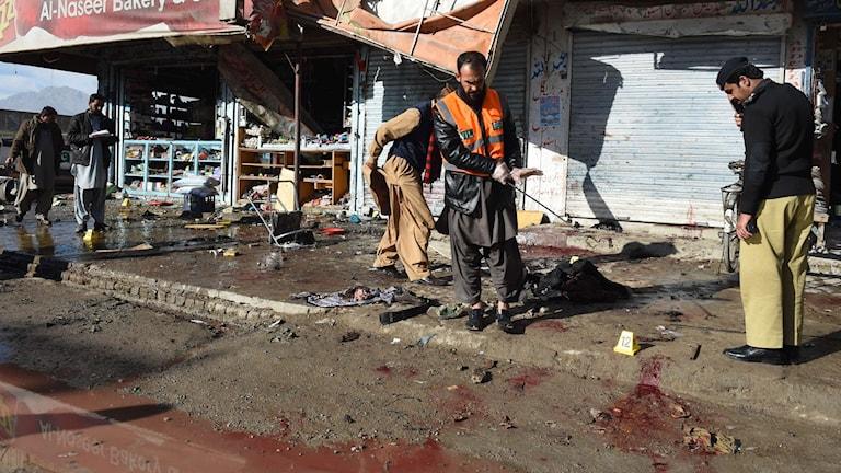 Människor undersöker platsen där flera människor dödades i en attack vid ett vaccinationscentrum i staden Quetta i Pakistan. Foto: AFP PHOTO / BANARAS KHANT TT.