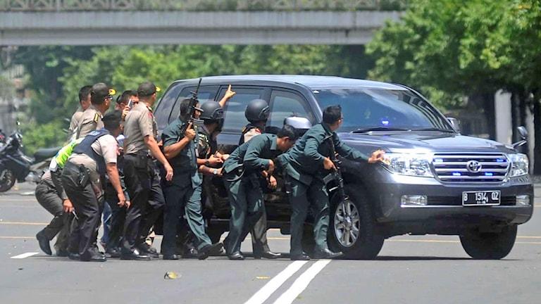 Poliser tar skydd bakom en bil vid terrorattentatet. Foto: AP/TT