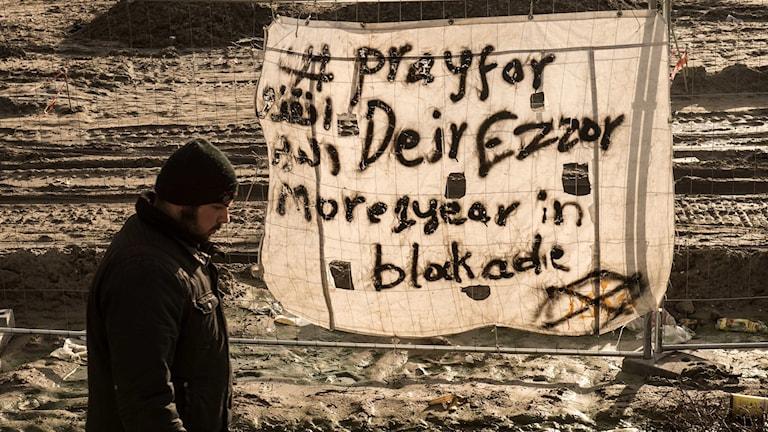 """Man går förbi ett baner med texten """"Be för Deir Ezzor"""" på engelska."""