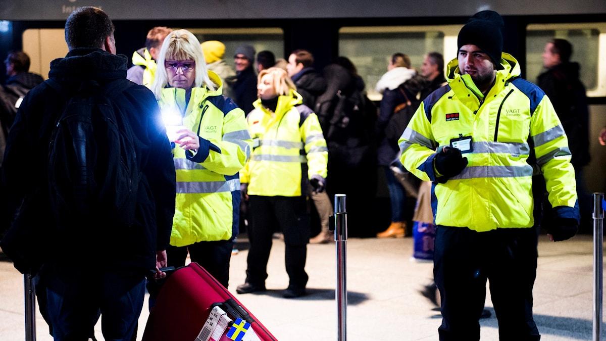 Ljusgrönklädda vakter kontrollerar ID av passagerare