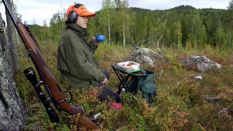 Ingela Olsson, älgjägare, tar en fikapaus på passet. Geväret står lutat mot ett träd