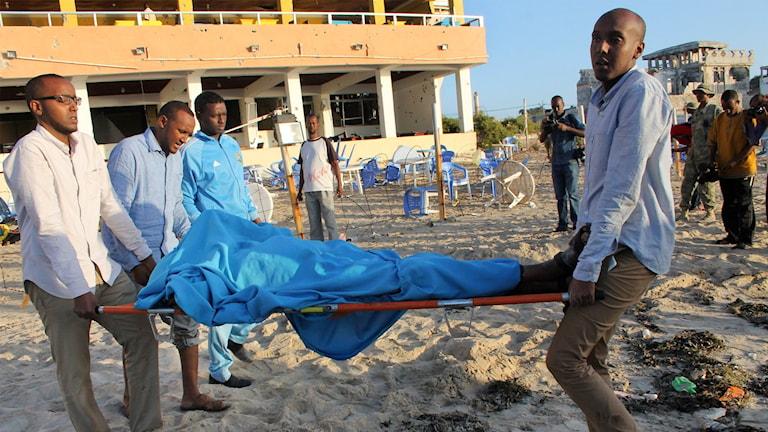 En övertäckt kropp bärs på en bår på en strand. Foto: Farah Abdi Warsameh/TT.