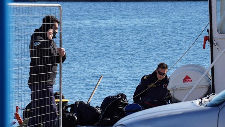 Två män från grekiska kustbevakningen på en båt. Foto: Dimitris Drosos/TT.