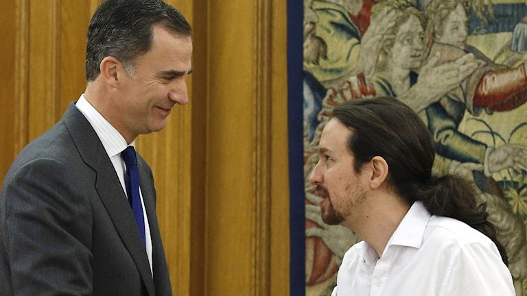 Spaniens Kung Felipe skakar hand med Podemos partiledare Pablo Iglesias.