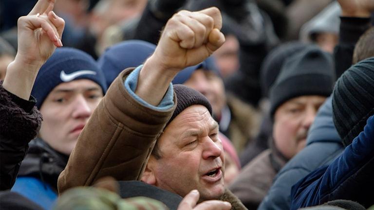 Man som lyfter en knuten näve i protest. Foto: Roveliu Buga/TT.