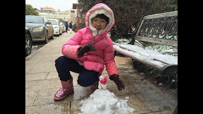 Iskyla har chockat östasien, men åttaåriga Huo Yixuan i Kunming passar på att bygga en snögubbe under palmerna. Foto: Hanna Sahlberg/SR.