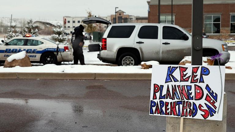 """""""Behåll Planned Parenhood säkert"""" står dte på en skylt med bil i bakgrunden."""