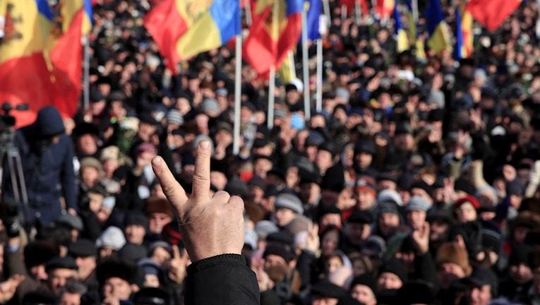 Man som visar ett segertecken med en folkmassa i bakgrunden.