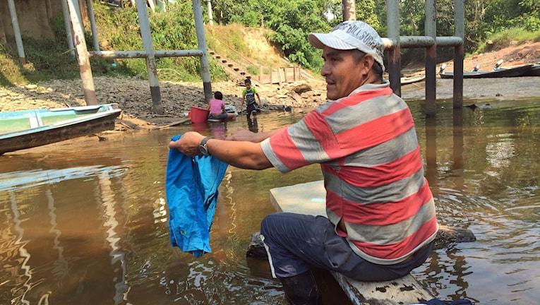 Man tvättar kläder i en smutsig flod.