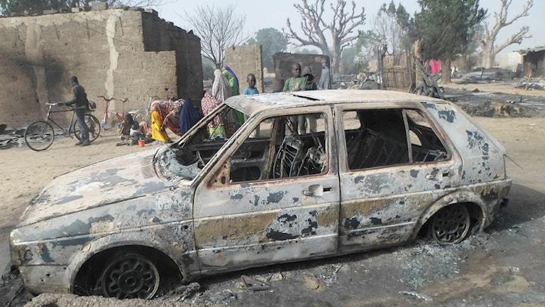 Barn samlas kring en utbränd bil i byn Dalori. Foto: Jossy Ola/TT.