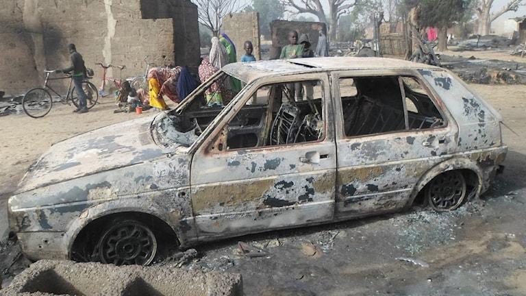 Barn vid en utbränd bil i byn Dalori. Foto: AP Photo/Jossy Ola