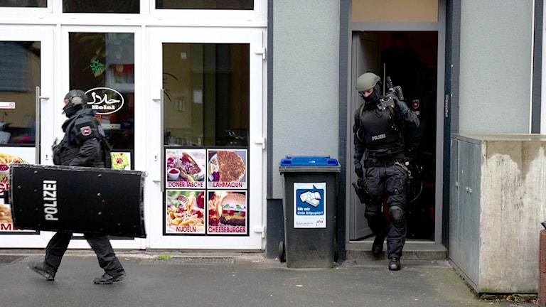 Polisen kommer ut efter razzia i en lägenhet i Hannover på torsdagsmorgonen.