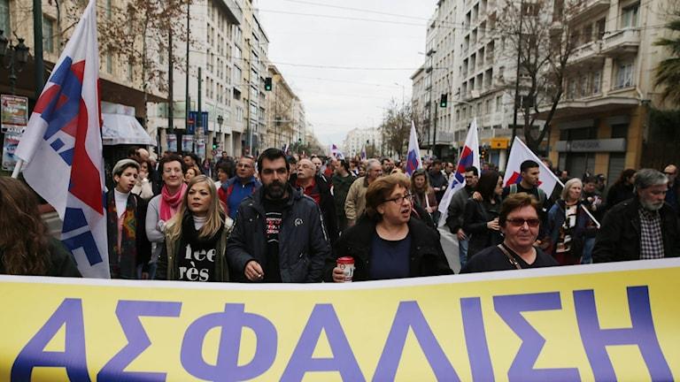 """Demonstranter från fackrörelsens koordinationscenter PAME håller en banderoll där det står """"social trygghet""""."""