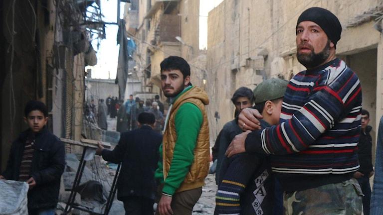 Man håller om ett barn i rebellkontrollerat område i Aleppo i Syrien. Foto: Thaer Mohammed/TT.
