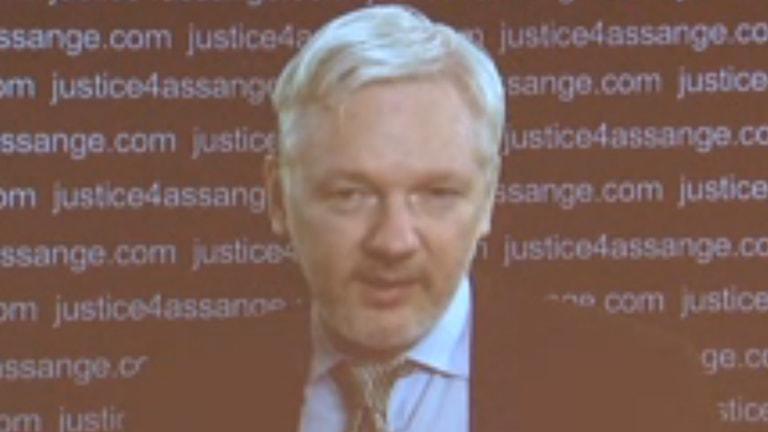 Julian Assange håller presskonferens via videolänk. Foto: Reuters.