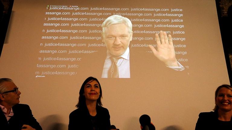 Julian Assange håller presskonferens via videolänk i London.