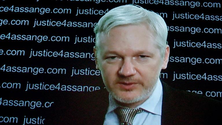 Julian Assange på skärm när han talar till media från Ecuadors ambassad i London.