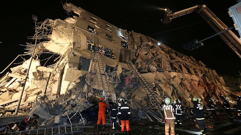 Räddningsarbetare genomsöker raserad byggnad efter jordbävning i Taiwan.