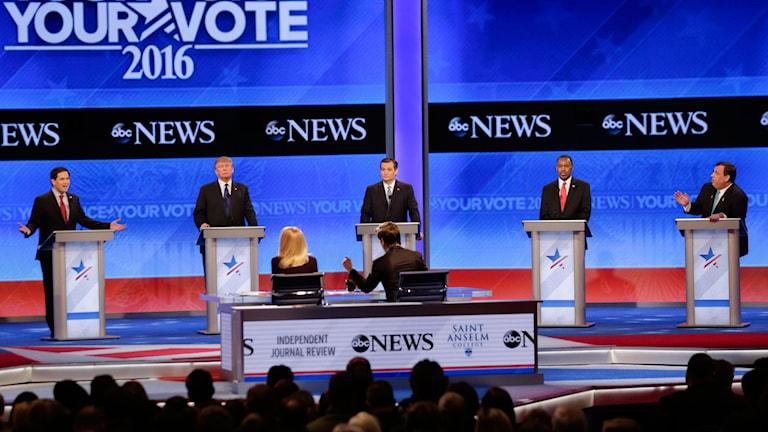 Fem män i blå kostymer och slipsar bakom varsin pulpet mot blå bakgrund inför publik.