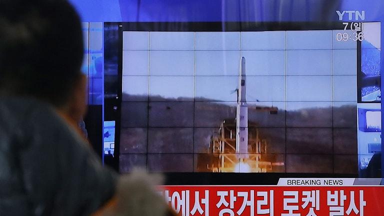 Man tittar på raketuppskjutning på teveskärm