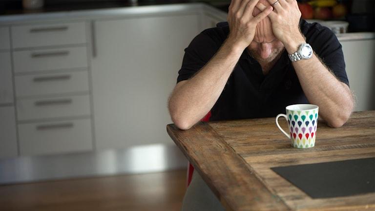 En deprimerad man sitter ensam hemma vid köksbordet