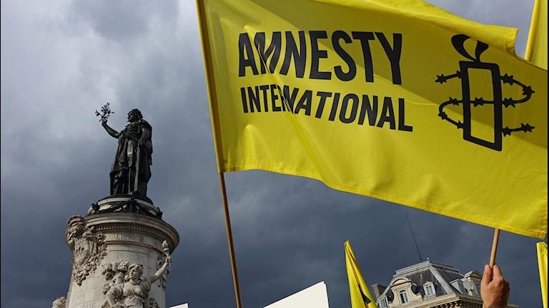 Amnestyflagga bredvid en staty.