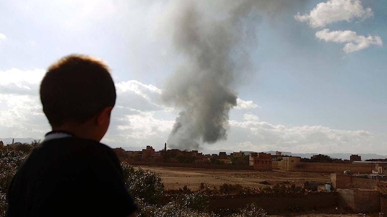 En jemenitisk pojke tittar på rök som stiger upp efter flygattacker.