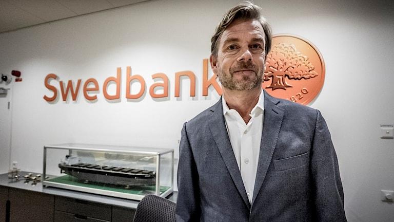 Michael Wolf Swedbank avgående vd framför Swedbank skylt
