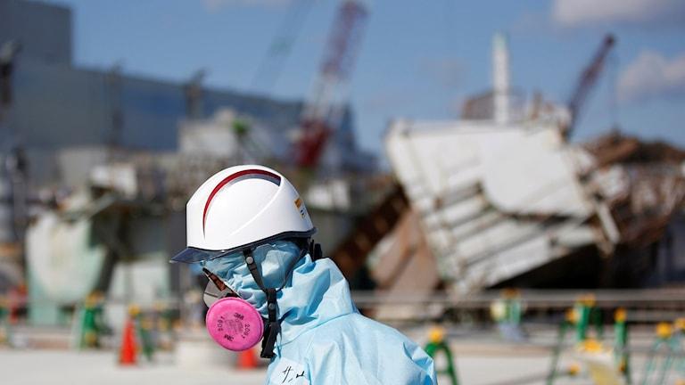 arbetare i hjälm framför kärnkraftverk
