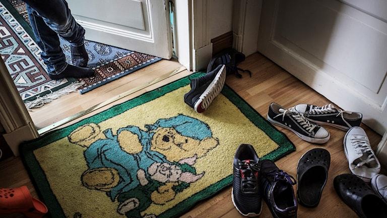 Dörrmatta och skor vid asylboende.
